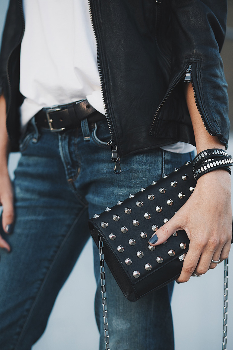 Detailed look at the 3/4 sleeve leather jackets Cafe Racer by R13, distressed Racer jeans by Citizens of Humanity, studded handbag by Michael Kors, and wrap bracelet by Calleen Cordero.